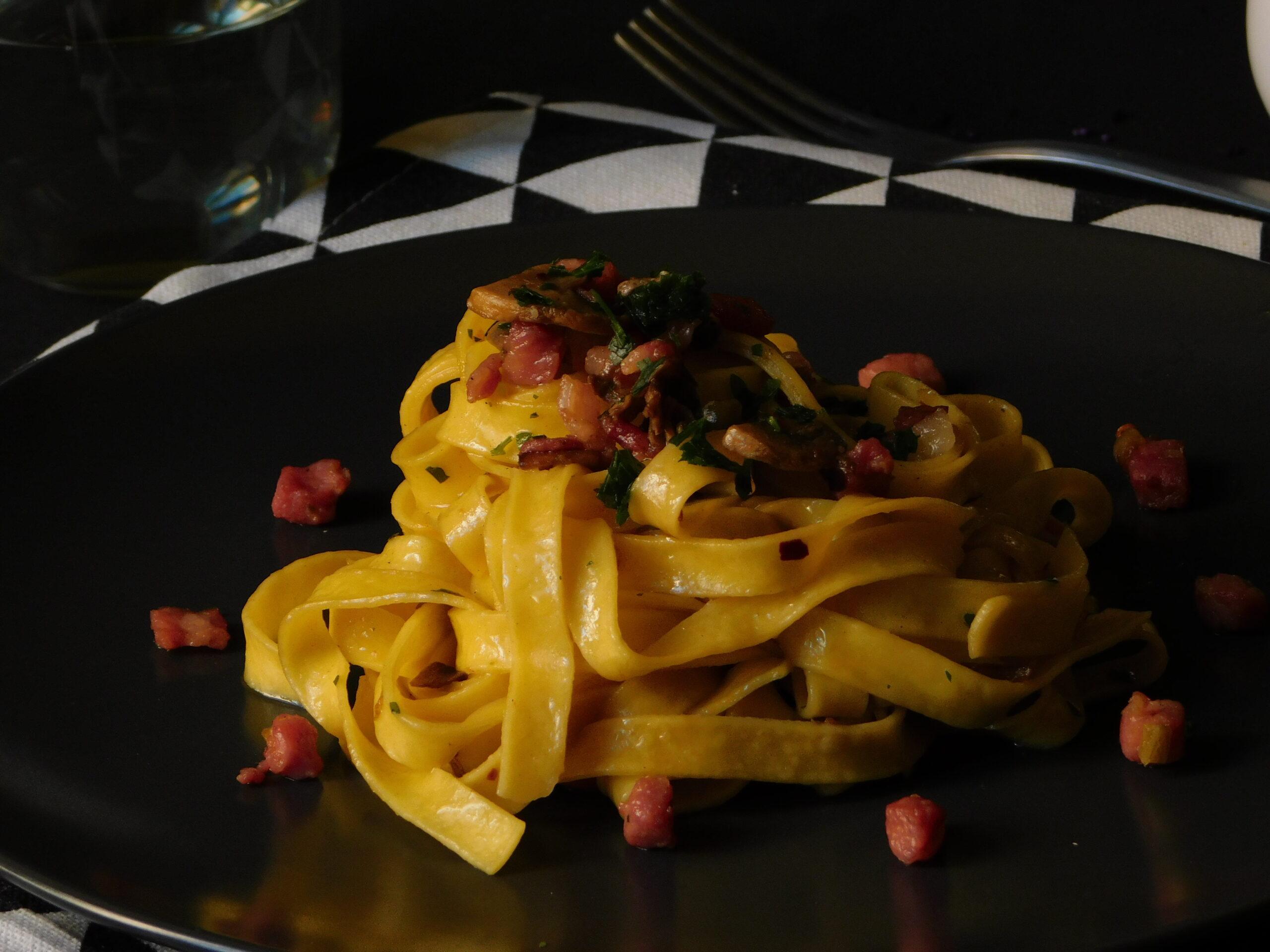 Tagliatelle saltate con peperoncino, funghi, pancetta e pisellini