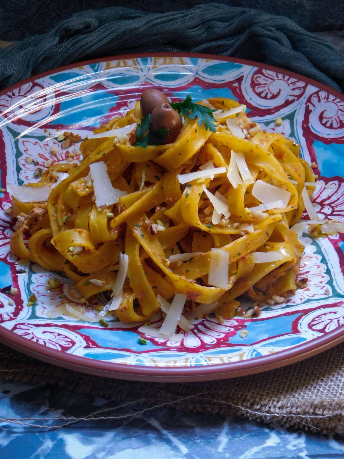 agliatelle al pesto di carciofi e pomodori secchi accompagnate da granella di pistacchi e nocciole, scaglie e un filo d'olio extra vergine di oliva